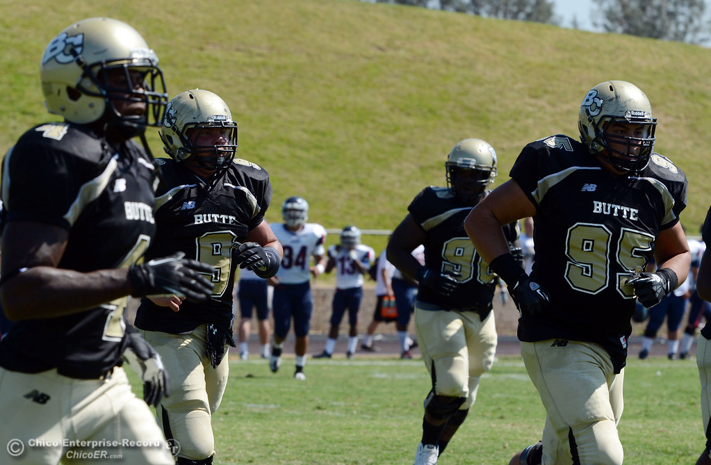 . Butte College\'s #9 Tyler Adair (left) and #95 Mark Rosenquist (Right) come off the field against College of the Siskiyous in the first quarter of their football game at Butte\'s Cowan Stadium on Saturday, September 14, 2013, in Oroville, Calif. (Jason Halley/Chico Enterprise-Record)