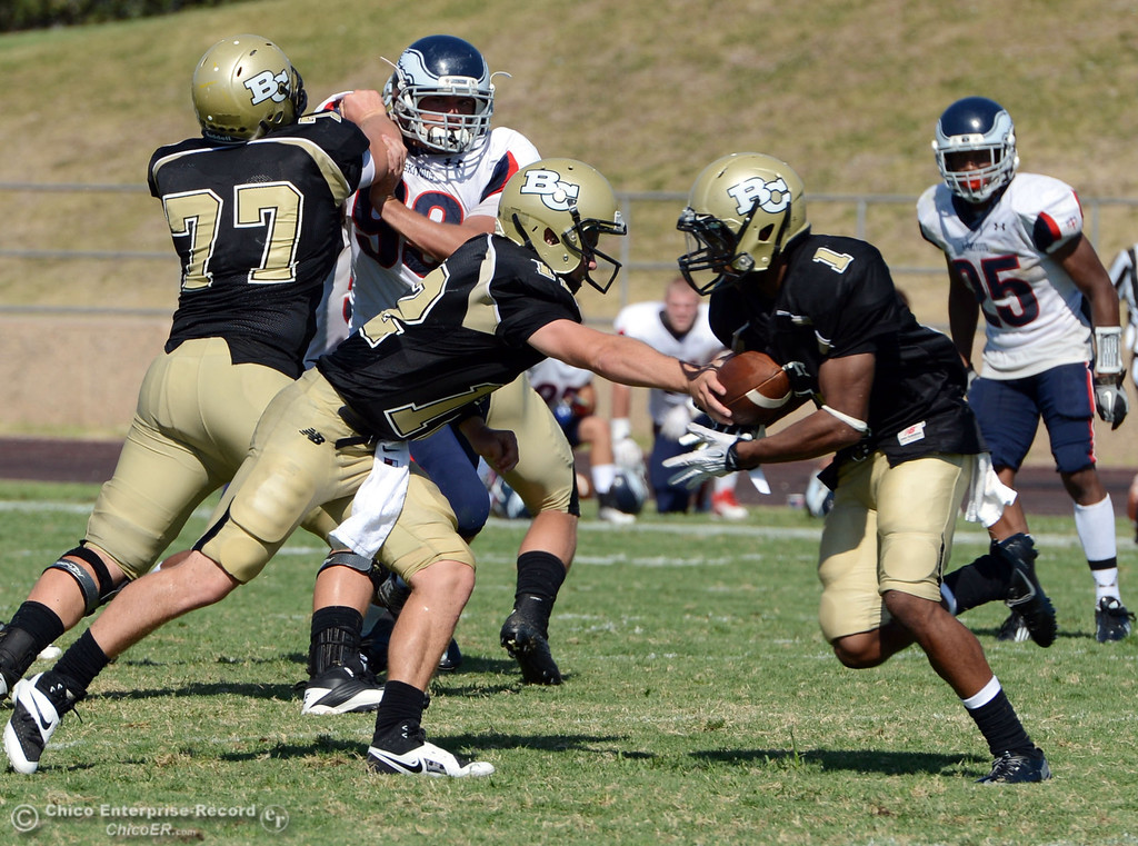 . Butte College\'s #12 Thomas Stuart (left) hands off to #1 Wes McCoy (right) against College of the Siskiyous in the third quarter of their football game at Butte\'s Cowan Stadium on Saturday, September 14, 2013, in Oroville, Calif. (Jason Halley/Chico Enterprise-Record)