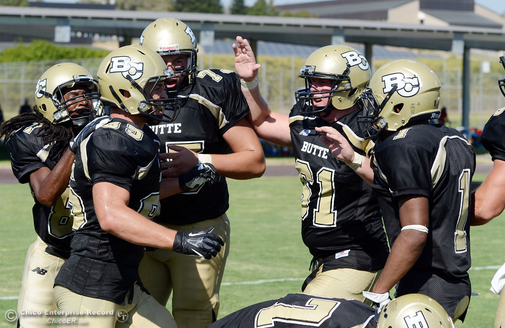 . Butte College\'s team congratulates #85 Richard Murphy on a touchdown against College of the Siskiyous in the third quarter of their football game at Butte\'s Cowan Stadium on Saturday, September 14, 2013, in Oroville, Calif. (Jason Halley/Chico Enterprise-Record)