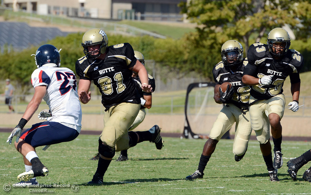 . Butte College\'s #61 Jacob Bigham (left) blocks for #48 Michael Faggett (left) who rushes behind #23 Mykah Hester (right) against College of the Siskiyous\' #27 Taylor Palade (left) in the fourth quarter of their football game at Butte\'s Cowan Stadium on Saturday, September 14, 2013, in Oroville, Calif. (Jason Halley/Chico Enterprise-Record)