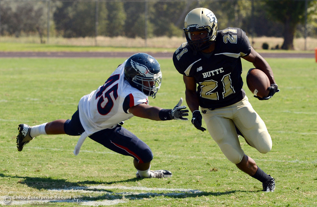 . Butte College\'s #21 Marvel Harris (right) rushes against College of the Siskiyous\' #45 Kerry Stabler (left) in the second quarter of their football game at Butte\'s Cowan Stadium on Saturday, September 14, 2013, in Oroville, Calif. (Jason Halley/Chico Enterprise-Record)