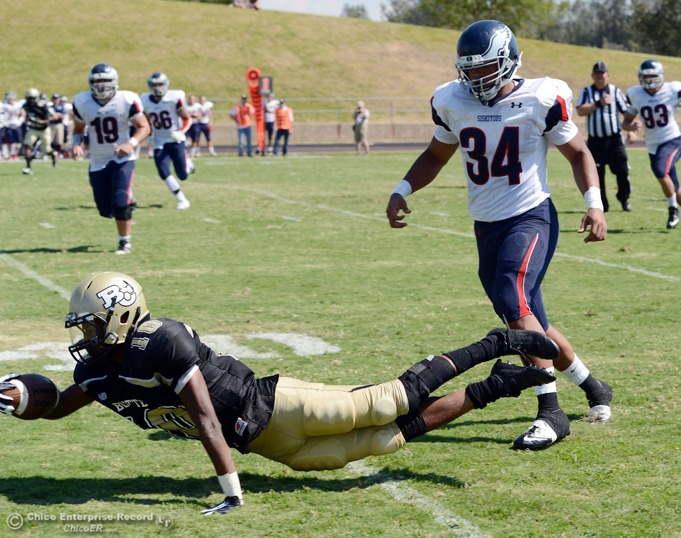 . Butte College\'s #10 CJ Grice (left) reaches for an extra yard against College of the Siskiyous\' #34 Anthony Ocasio (right) in the second quarter of their football game at Butte\'s Cowan Stadium on Saturday, September 14, 2013, in Oroville, Calif. (Jason Halley/Chico Enterprise-Record)
