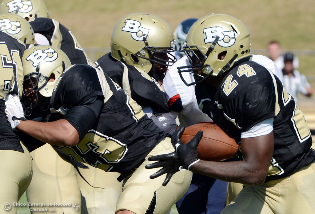 . Butte College\'s #24 Kendall Williams (right) rushes against College of the Siskiyous in the third quarter of their football game at Butte\'s Cowan Stadium on Saturday, September 14, 2013, in Oroville, Calif. (Jason Halley/Chico Enterprise-Record)