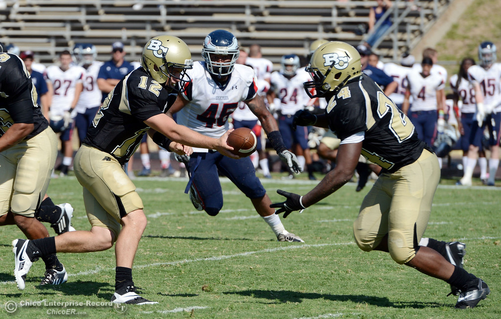 . Butte College\'s #12 Thomas Stuart (left) hands off to #24 Kendall Williams (right) against College of the Siskiyous in the third quarter of their football game at Butte\'s Cowan Stadium on Saturday, September 14, 2013, in Oroville, Calif. (Jason Halley/Chico Enterprise-Record)