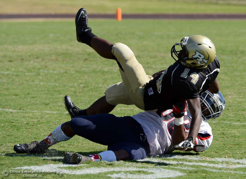 . Butte College\'s #14Robert Frazier (top) is tackled against College of the Siskiyous\' #58 Tyrese Lyons (bottom) in the third quarter of their football game at Butte\'s Cowan Stadium on Saturday, September 14, 2013, in Oroville, Calif. (Jason Halley/Chico Enterprise-Record)
