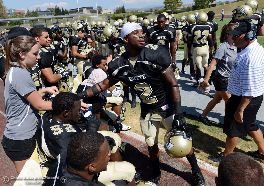 . Butte College\'s #2 Deonte Flemings (center) grabs a water against College of the Siskiyous in the first quarter of their football game at Butte\'s Cowan Stadium on Saturday, September 14, 2013, in Oroville, Calif. (Jason Halley/Chico Enterprise-Record)