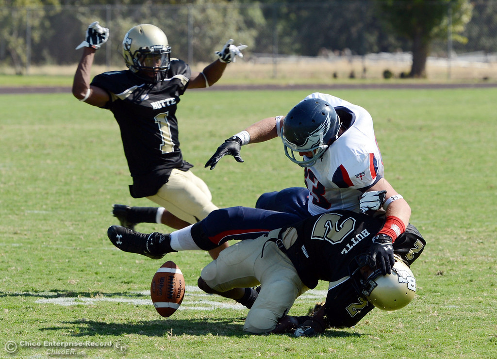 . Butte College\'s #1 Wes McCoy (left) watches a fumble caused by #2 Deonte Flemings (bottom) against College of the Siskiyous\' #83 Cale Backinger (center) in the third quarter of their football game at Butte\'s Cowan Stadium on Saturday, September 14, 2013, in Oroville, Calif. (Jason Halley/Chico Enterprise-Record)