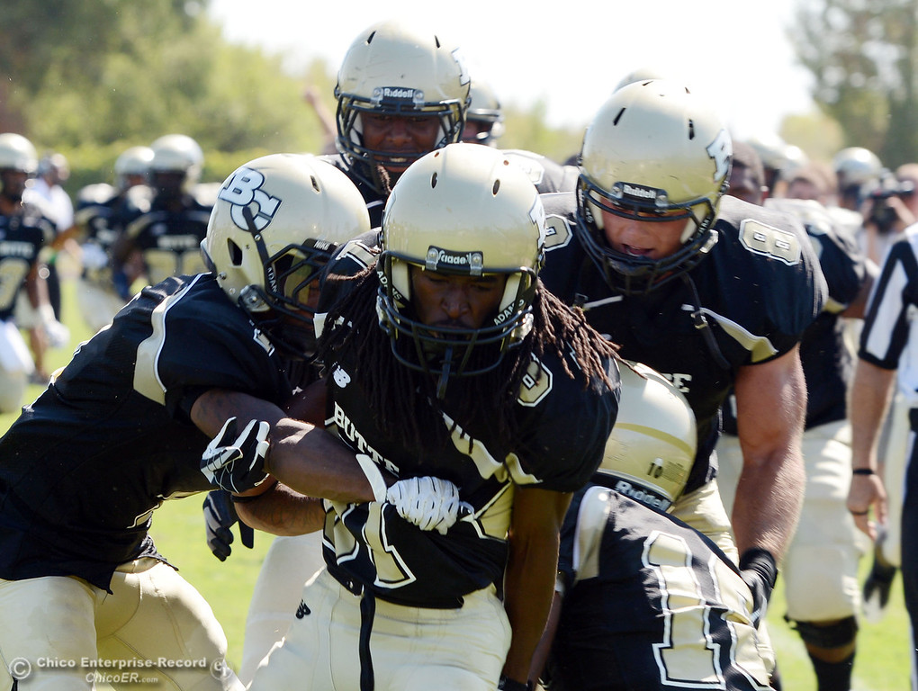 . Butte College\'s team congratulates #87 Timazray Shepherd (center) on scoring for a touchdown against College of the Siskiyous in the second quarter of their football game at Butte\'s Cowan Stadium on Saturday, September 14, 2013, in Oroville, Calif. (Jason Halley/Chico Enterprise-Record)
