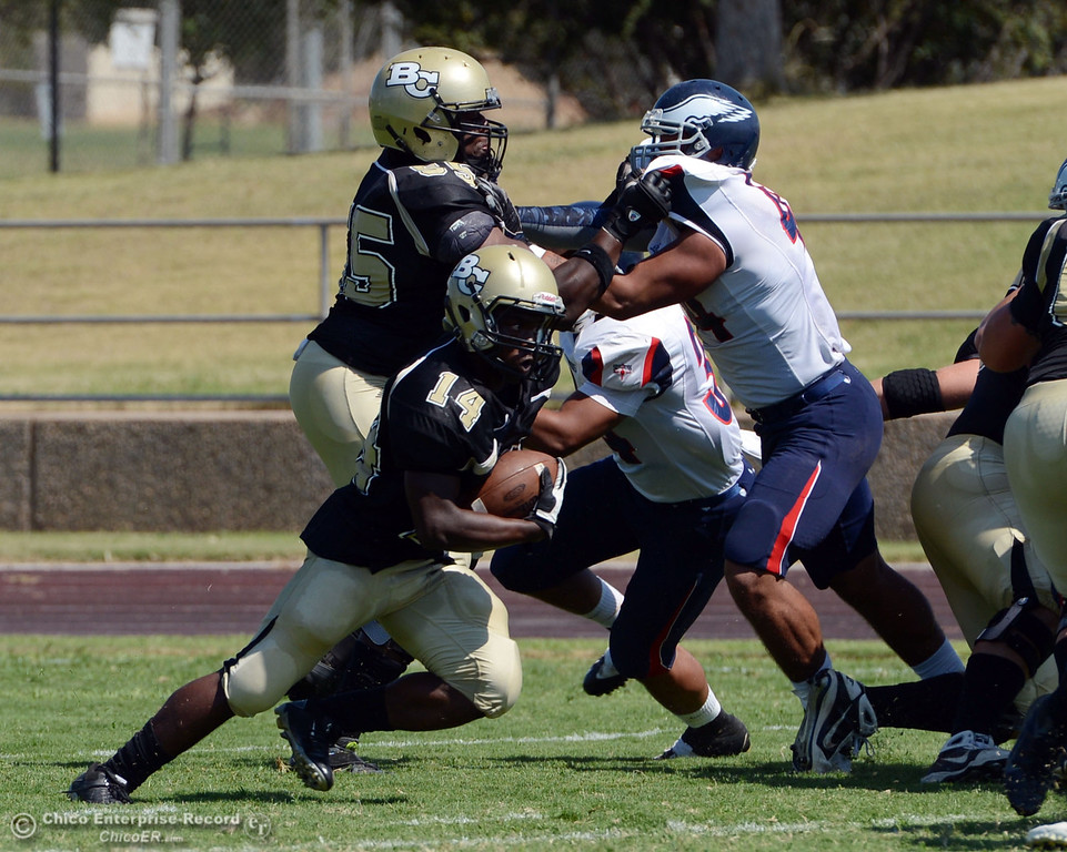 . Butte College\'s #14 Robert Frazier (center) rushes against College of the Siskiyous in the first quarter of their football game at Butte\'s Cowan Stadium on Saturday, September 14, 2013, in Oroville, Calif. (Jason Halley/Chico Enterprise-Record)