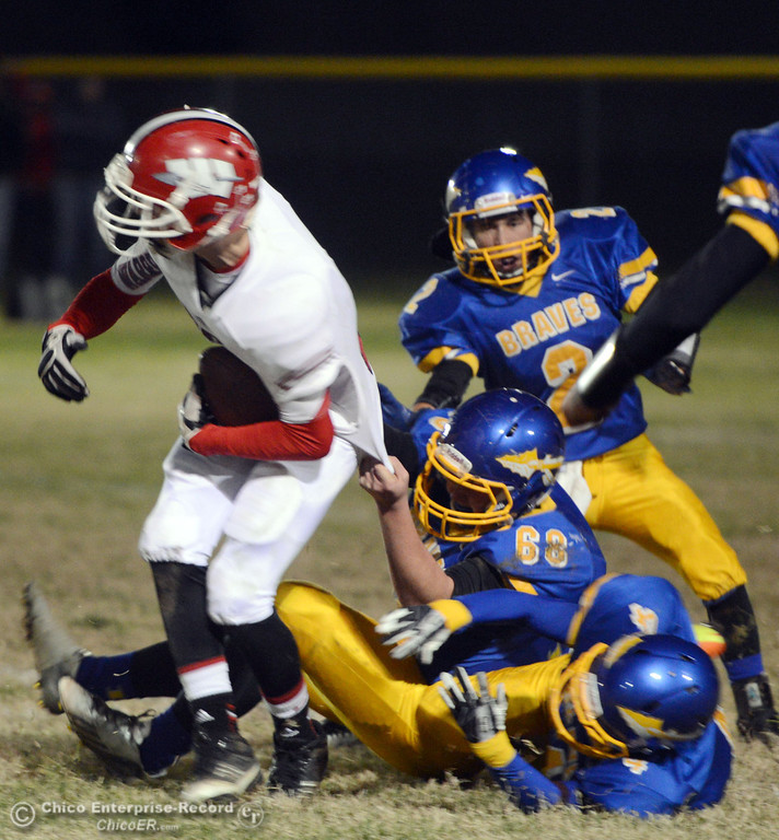 . Hamilton High\'s #68 Riley Meridith (center) with #4 Angel Montes (bottom) and #2 Theron Fumasi (top) tackle against Winters High\'s #2 Christian Corrales (left) in the first quarter of their football game at HHS on Wednesday, November 27, 2013 in Hamilton City, CA.  (Jason Halley/Chico Enterprise-Record)