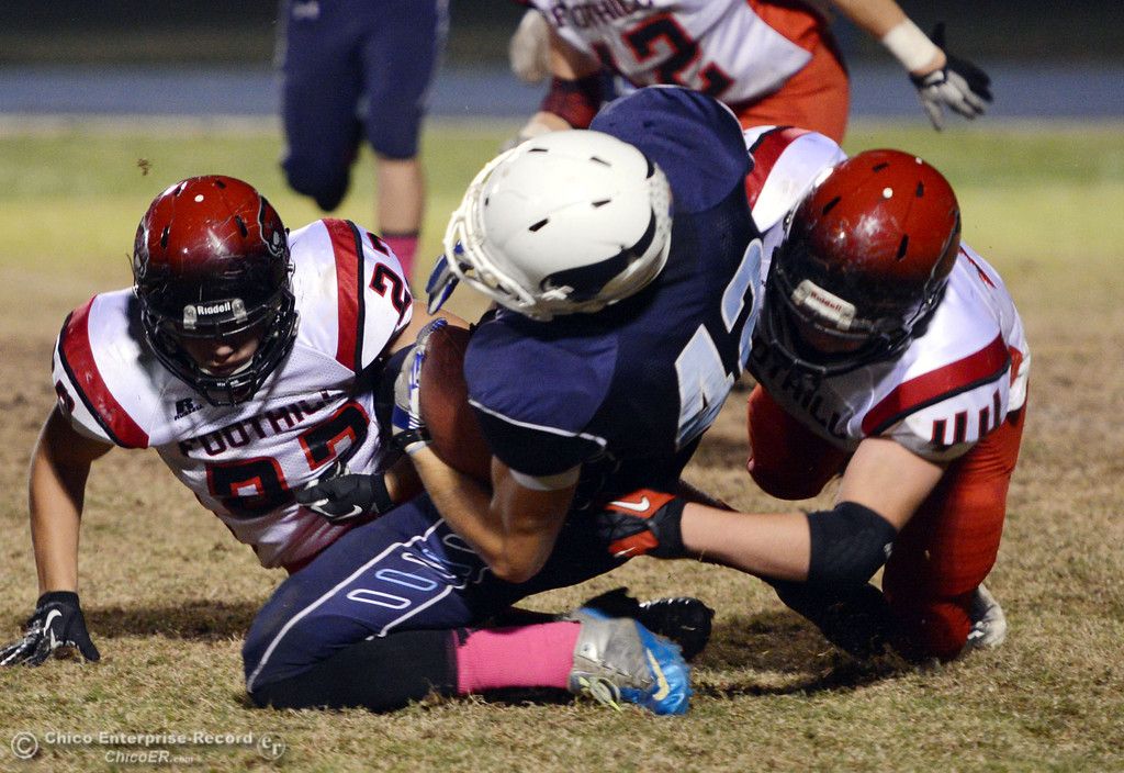 . Pleasant Valley High\'s #42 Chad Olsen (center) is tackled against Foothill High\'s #44 Drew Faircloth (right) and #23 Zac Thompson (left) in the second quarter of their football game at PVHS Asgard Yard Friday, October 11, 2013 in Chico, Calif.  (Jason Halley/Chico Enterprise-Record)