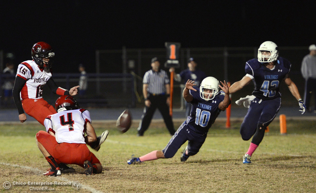 . Pleasant Valley High\'s #10 Tucker LaRue (mid right) and #42 Chad Olsen (far right) attempt to block against Foothill High\'s #15 Ryan Pollard (far left) extra point kick on a hold by #4 Luke Kelly (mid left) in the second quarter of their football game at PVHS Asgard Yard Friday, October 11, 2013 in Chico, Calif.  (Jason Halley/Chico Enterprise-Record)