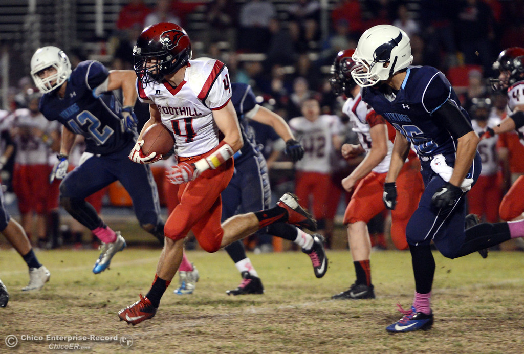 . Foothill High\'s #4 Luke Kelly (center) carries back the ball after an interception against Pleasant Valley High in the third quarter of their football game at PVHS Asgard Yard Friday, October 11, 2013 in Chico, Calif.  (Jason Halley/Chico Enterprise-Record)