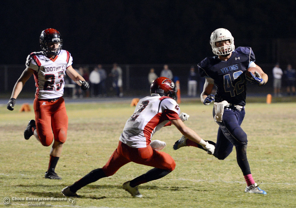 . Pleasant Valley High\'s #42 Chad Olsen (right) rushes against Foothill High\'s #2 Chandler Roe (center) and #23 Zac Thompson (left) in the fourth quarter of their football game at PVHS Asgard Yard Friday, October 11, 2013 in Chico, Calif.  (Jason Halley/Chico Enterprise-Record)