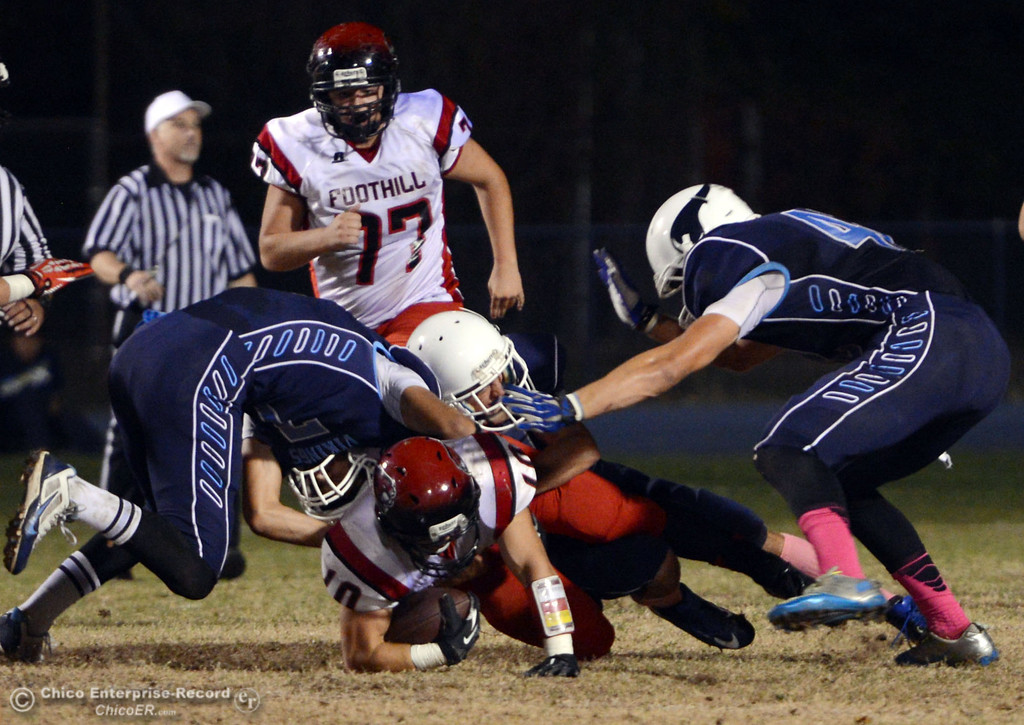 . Pleasant Valley High\'s #7 Zane Ferguson, #10 Tucker LaRue and #42 Chad Olsen (left to right) tackle against Foothill High\'s #10 Blake Burnett (center) in the first quarter of their football game at PVHS Asgard Yard Friday, October 11, 2013 in Chico, Calif.  (Jason Halley/Chico Enterprise-Record)