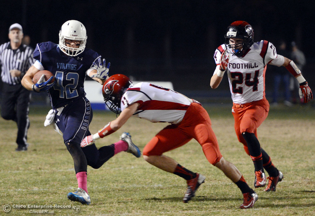 . Pleasant Valley High\'s #42 Chad Olsen (left) breaks a tackle against Foothill High\'s #4 Luke Kelly (center) as #24 Logan Beebe (right) looks on in the first quarter of their football game at PVHS Asgard Yard Friday, October 11, 2013 in Chico, Calif.  (Jason Halley/Chico Enterprise-Record)