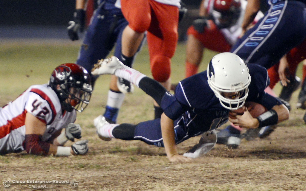 . Pleasant Valley High\'s #12 Trent Darms (right) is tripped up against Foothill High\'s #42 Tyler Duclos (left) in the first quarter of their football game at PVHS Asgard Yard Friday, October 11, 2013 in Chico, Calif.  (Jason Halley/Chico Enterprise-Record)