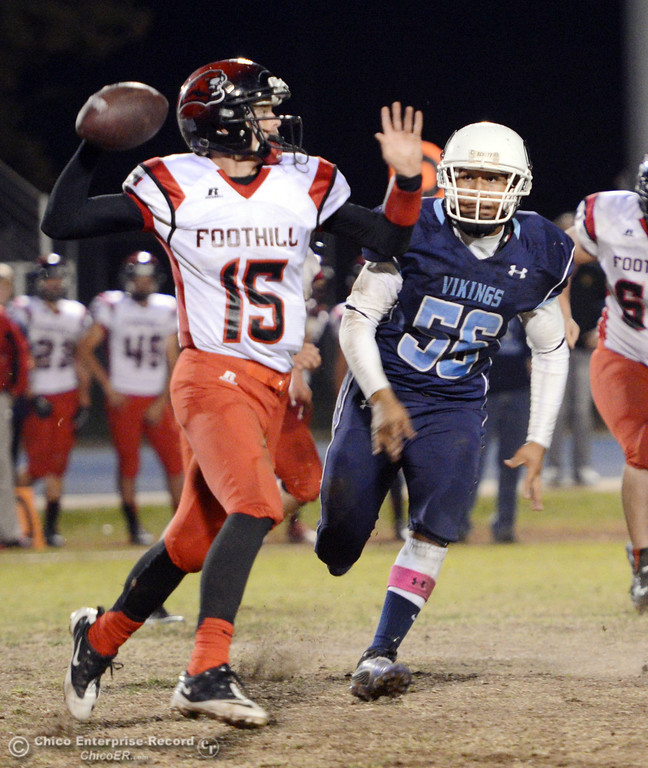 . Pleasant Valley High\'s #56 Zariel Torres (center) pressures against Foothill High\'s #15 Ryan Pollard (left) in the fourth quarter of their football game at PVHS Asgard Yard Friday, October 11, 2013 in Chico, Calif.  (Jason Halley/Chico Enterprise-Record)
