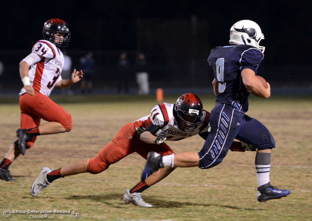 . Pleasant Valley High\'s #9 Houston McGowan (right) rushes against Foothill High\'s #11 Ryan Terras (left) in the third quarter of their football game at PVHS Asgard Yard Friday, October 11, 2013 in Chico, Calif.  (Jason Halley/Chico Enterprise-Record)