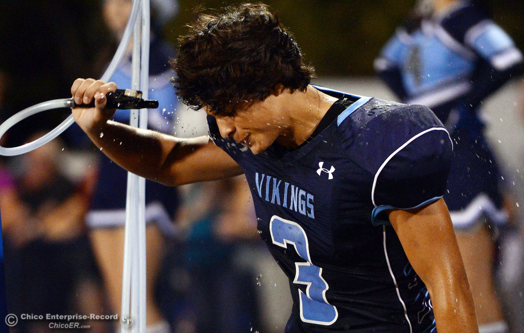 . Pleasant Valley High\'s #3 Brandon Romero pours water on his head against Lassen High in the second quarter of their football game at PVHS Asgard Yard Friday, September 6, 2013 in Chico, Calif. (Jason Halley/Chico Enterprise-Record)