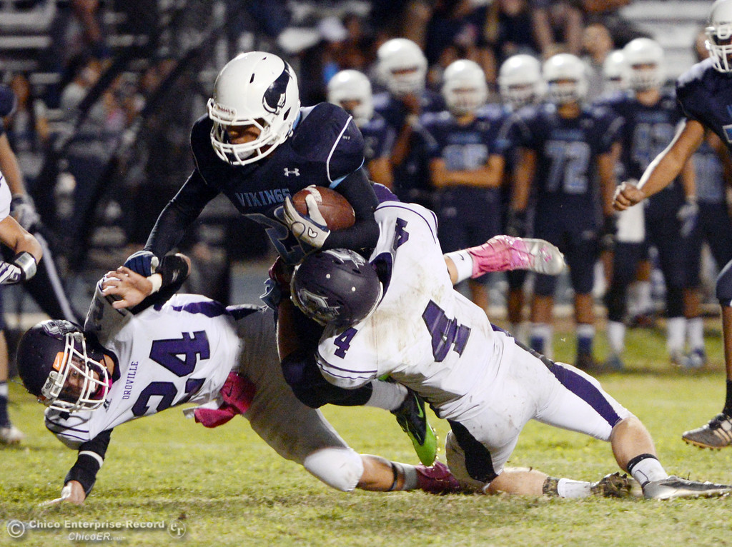 . Pleasant Valley High\'s #20 Bryan Esquivel (center) is tackled against Oroville High\'s #4 Antony Ramsey (right) in the fourth quarter of their football game at PVHS Asgard Yard Friday, September 20, 2013, in Chico, Calif. (Jason Halley/Chico Enterprise-Record)