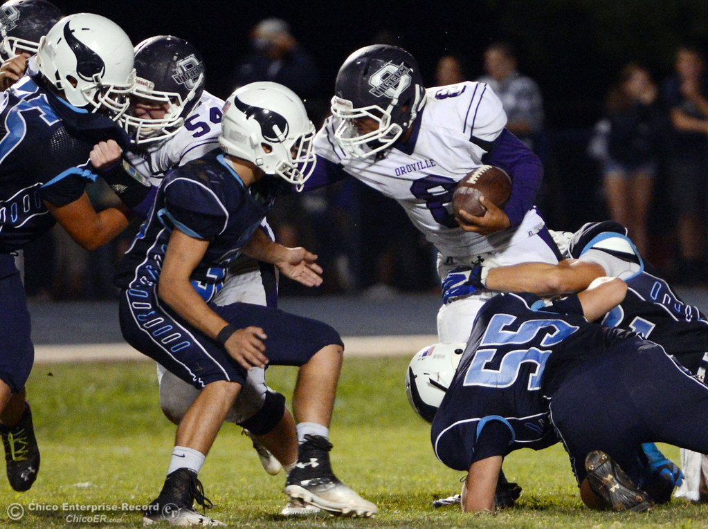 . Oroville High\'s #8 James Jones (center) is tackled against Pleasant Valley High in the third quarter of their football game at PVHS Asgard Yard Friday, September 20, 2013, in Chico, Calif. (Jason Halley/Chico Enterprise-Record)