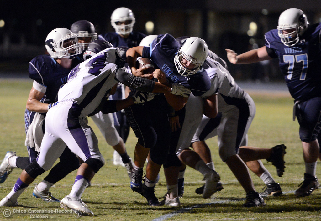 . Pleasant Valley High\'s #9 Houston McGowan (center) rushes against Oroville High\'s #44 Derrek Gordon (left) in the second quarter of their football game at PVHS Asgard Yard Friday, September 20, 2013, in Chico, Calif. (Jason Halley/Chico Enterprise-Record)