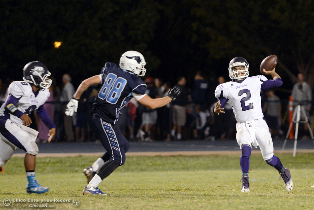 . Oroville High\'s #2 Marcus Wilhite (right) passes under pressure from Pleasant Valley High\'s #88 Zack Suttles (left) in the third quarter of their football game at PVHS Asgard Yard Friday, September 20, 2013, in Chico, Calif. (Jason Halley/Chico Enterprise-Record)