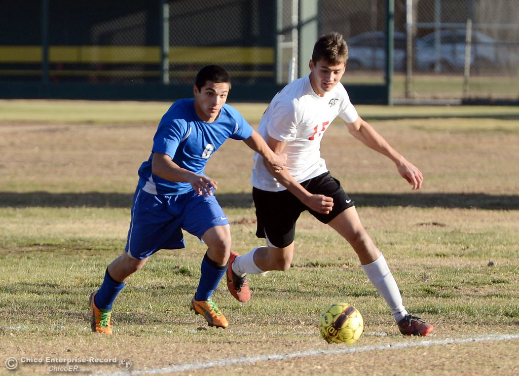 . Chico High\'s #15  Bailey Gripenstraw (right) battles against Orland High\'s #6 Hector Gutierrez in the first half of their boys soccer game at CHS Thursday, December 19, 2013 in Chico, Calif. (Jason Halley/Chico Enterprise-Record)