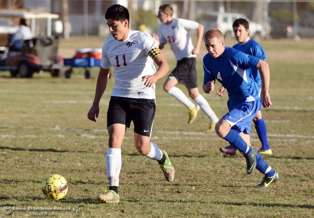 . Chico High\'s #11 Jim Carrillo (left) battles against Orland High\'s #4 Devin James (right) in the first half of their boys soccer game at CHS Thursday, December 19, 2013 in Chico, Calif. (Jason Halley/Chico Enterprise-Record)