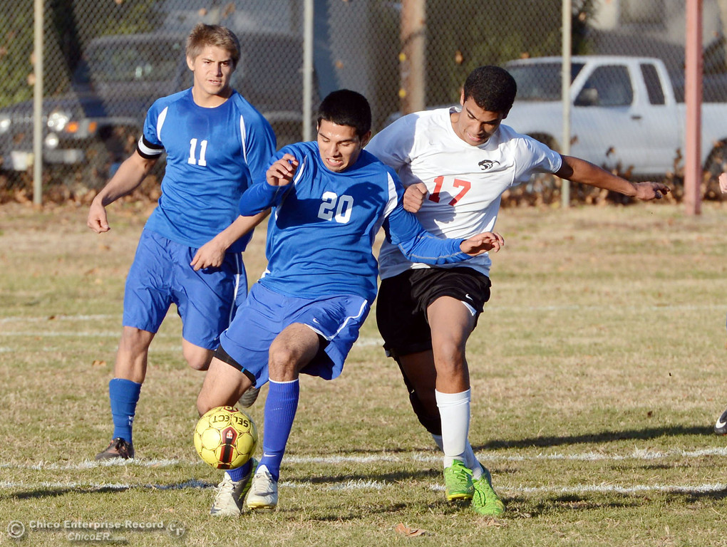 . Chico High\'s #17 Omar Carey (right) battles against Orland High\'s #20 Jesse Gonzalez (center) as #11 Mirsha Rosas (left) looks on in the first half of their boys soccer game at CHS Thursday, December 19, 2013 in Chico, Calif. (Jason Halley/Chico Enterprise-Record)