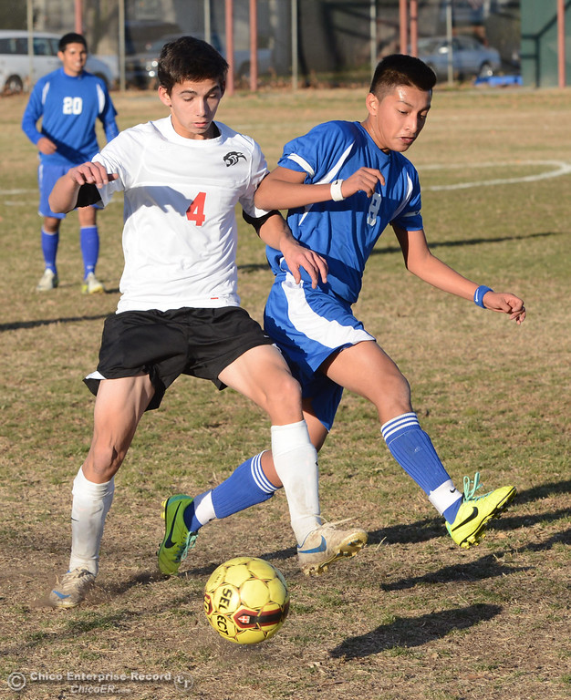 . Chico High\'s #4 Jack Chinchay (left) battles against Orland High\'s #8 Israel Zintzun (right) in the first half of their boys soccer game at CHS Thursday, December 19, 2013 in Chico, Calif. (Jason Halley/Chico Enterprise-Record)