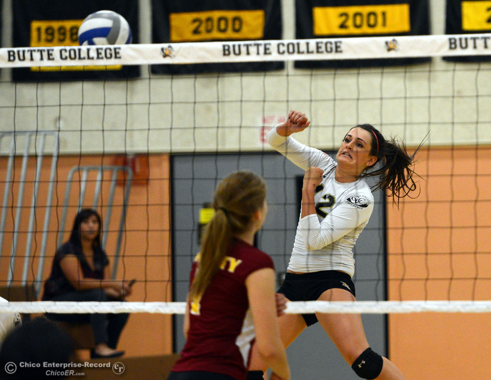 . Butte College\'s #12 Callie Flood (right) spikes against Sac City College in the second game of their women\'s volleyball match at Butte\'s Cowan Gym Wednesday, September 25, 2013, in Oroville, Calif.  (Jason Halley/Chico Enterprise-Record)