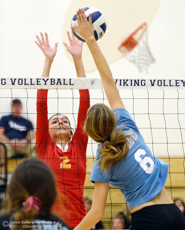 . Pleasant Valley High\'s #6 Hanne Henriksen (right) spikes against Chico High\'s #2 Sydney Gaskey (left) in the second game of their girls volleyball match at PVHS Varley Gym Saturday, October 12, 2013 in Chico, Calif.  (Jason Halley/Chico Enterprise-Record)
