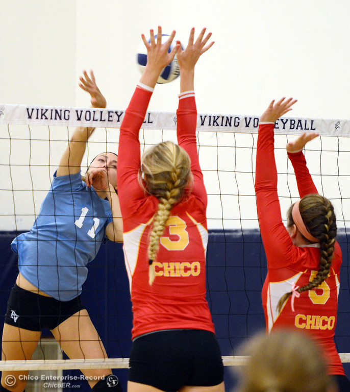 . Pleasant Valley High\'s #11 Heather Pemebroke (left) spikes against Chico High\'s #3 KC Sicheneder (center) and #5 Amanda Manning in the first game of their girls volleyball match at PVHS Varley Gym Saturday, October 12, 2013 in Chico, Calif.  (Jason Halley/Chico Enterprise-Record)