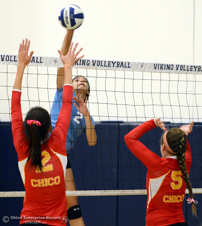 . Pleasant Valley High\'s #2 Lily Justine (center) spikes against Chico High\'s #2 Sydney Gaskey (left) and #5 Amanda Manning (right) in the first game of their girls volleyball match at PVHS Varley Gym Saturday, October 12, 2013 in Chico, Calif.  (Jason Halley/Chico Enterprise-Record)