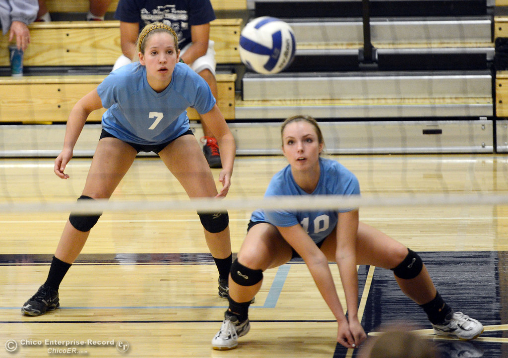 . Pleasant Valley High\'s #7 Meagan Mason (left) watches #10 Ashley Geiger (right) go in for a dig against Chico High in the first game of their girls volleyball match at PVHS Varley Gym Saturday, October 12, 2013 in Chico, Calif.  (Jason Halley/Chico Enterprise-Record)