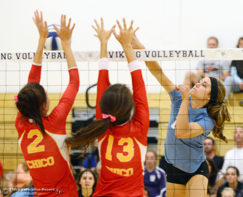 . Pleasant Valley High\'s #11 Heather Pemebroke (right) spikes against Chico High\'s #13 Becca Korte (center) and #2 Sydney Gaskey (left) in the second game of their girls volleyball match at PVHS Varley Gym Saturday, October 12, 2013 in Chico, Calif.  (Jason Halley/Chico Enterprise-Record)