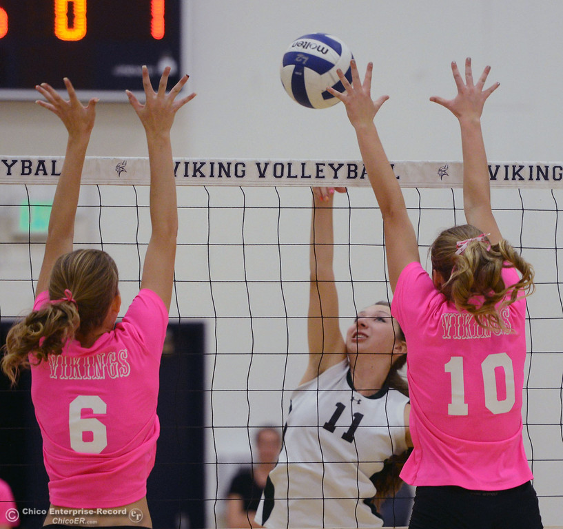 ". Pleasant Valley High\'s #6 Hanne Henriksen (left) and #10 Ashley Geiger (right) attempt to block against Paradise High\'s #11 Jennifer Olson (center) in the second game of their volleyball match at PVHS Varley Gym Thursday, October 17, 2013 in Chico, Calif. PV volleyball wore pink instead of blue vs Paradise at ""Fight Like a Viking Night,\"" to raise money for cancer research. (Jason Halley/Chico Enterprise-Record)"