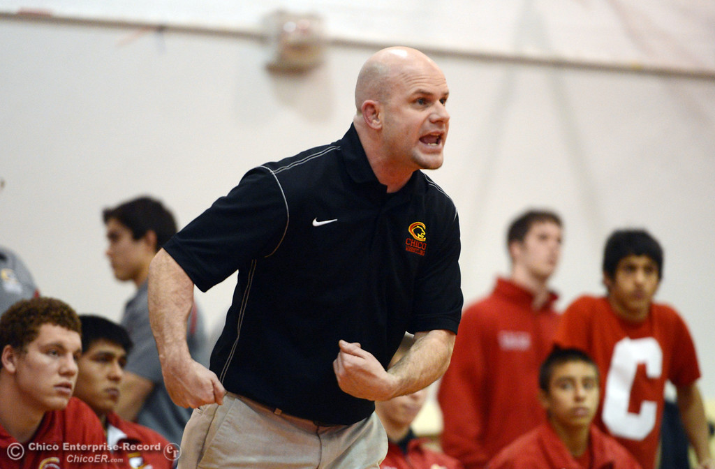 . Chico High\'s coach Keith Rollins coaches David Leyva, who wrestles against Orland High\'s Quinton Hill in the 145 lbs wrestling match at CHS Wednesday, December 18, 2013 in Chico, Calif. (Jason Halley/Chico Enterprise-Record)