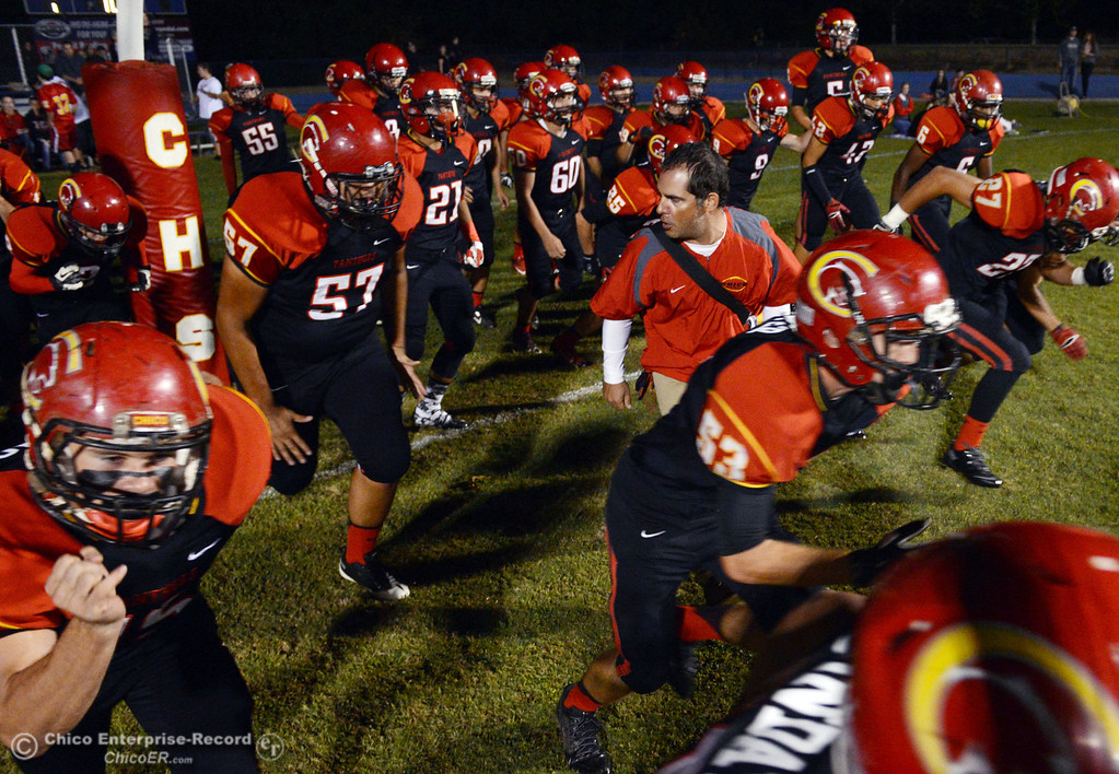 . Chico High coach Jason Alvistur (center) walks onto the field with his team against Central Valley High before the first quarter of their football game at Asgard Yard Friday, September 27, 2013, in Chico, Calif.  (Jason Halley/Chico Enterprise-Record)