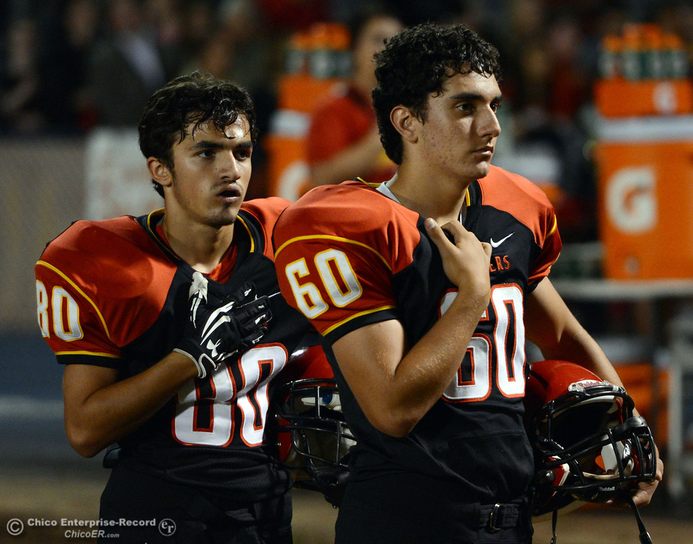 . Chico High\'s #80 Anthony Miller and #60 Joe Richmond (left to right) stand for the National Anthem against Central Valley High in the first quarter of their football game at Asgard Yard Friday, September 27, 2013, in Chico, Calif.  (Jason Halley/Chico Enterprise-Record)